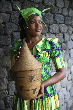 HMS3522646 Rwanda, Volcanoes National Park, young Rwandan woman in traditional dress, member of staff of Bisate Lodge, carrying a basketry