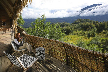 HMS3522648 Rwanda, Volcanoes National Park, woman drinking tea on the terrace of a suite at Bisate Lodge, a lodge of the Wilnderness safaris hotel group, open on Mount Bisoke