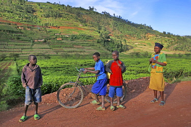 HMS3522655 Rwanda, center of the country, children in colorful clothes on a laterite track in the middle of green hills