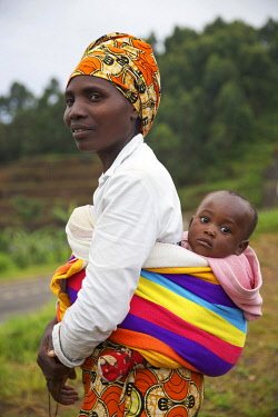 HMS3522660 Rwanda, Gisakura, woman wearing a colorful turban and carrying her baby in the back