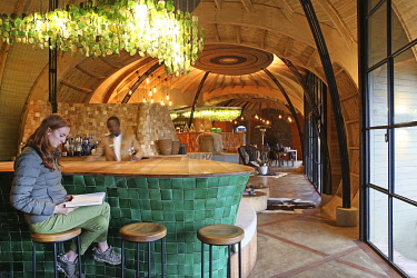HMS3522676 Rwanda, Volcanoes National Park, customer sitting at the bar of Bisate lodge, a lodge of Wilderness safaris group inspired by the former royal palace of Nyanza