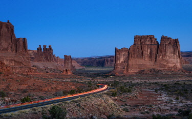 USA14935AW Cars entering rock formations The Organ, Tower of Babel, Sheep rock and Three Gossips via Arches Scenic Drive road at dawn, Arches National Park, Utah, USA
