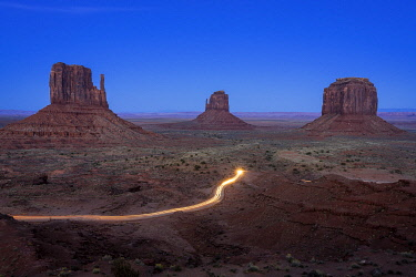 USA14949AW Light trail from car driving on scenic drive road near The Mitten Buttes in Monument Valley, Arizona, USA