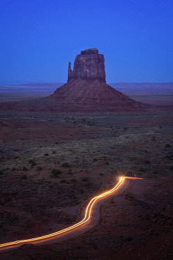 USA14950AW Light trail from car driving on scenic drive road near East Mitten Butte in Monument Valley, Arizona, USA