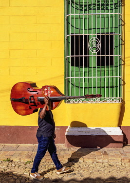 CUB2139AW Musician with his double bass walking through the colourful street of Trinidad, Sancti Spiritus Province, Cuba