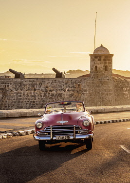 CUB2247AW Vintage Car at El Malecon with San Salvador de la Punta Castle in the background, sunrise, Havana, La Habana Province, Cuba
