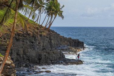 SAO1204AW Africa, S�A?o Tomè and Principe. Fisherman on the rocks of Boca do Inferno.