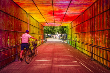 Sweden, Narke, Orebro, Slottsparken park, park brige draped with rainbow-colored plastic, with bicyclists, NR