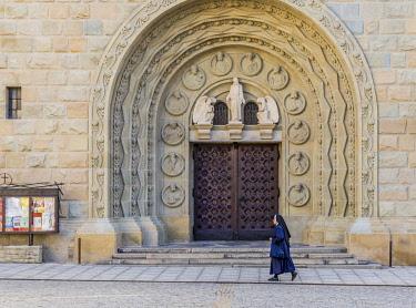 POL2439AW A nun walking past the Cathedral of St. Nicholas in Bielsko Biala,Silesian Voivodeship,Poland