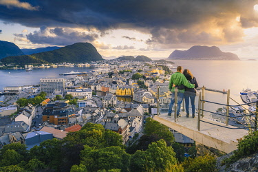 NOR1092AW Alesund, More og Romsdal, Norway. Couple admiring the cityscape at sunset from Byrampen lookout.