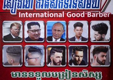 CMB1675AW Asia, Southeast Asia, Cambodia, Phnom Penh, hair dresser advert showing Putin, Kim Jong-un and Donald Trump