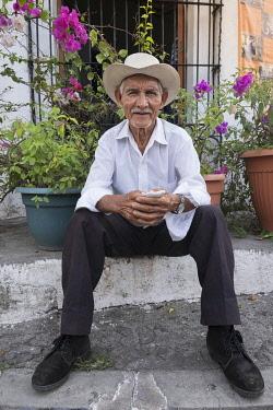 ELS0020AW Americas, Central America, El Salvador, Cuscatlan department, Suchitoto village, local campesino sitting on a doorstep