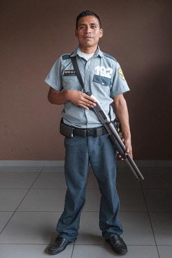 ELS0026AW Americas, Central America, El Salvador, security guard with a pump action shot gun