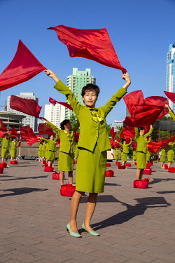NKO0456 North Korea, Pyongyang. Cheerleaders waving flags accompanied by patriotic music to encourage commuters on their way to work.