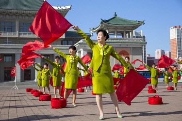 NKO0459 North Korea, Pyongyang. Cheerleaders waving flags accompanied by patriotic music to encourage commuters on their way to work.