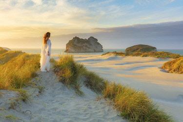 NZ9819AW A woman alone at Wharariki beach at sunset in the Abel Tasman national park