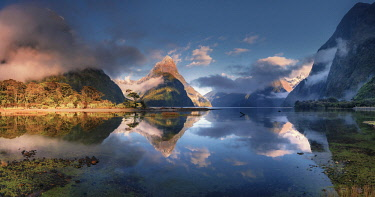 NZ9880AW Mitre Peak reflecting in the fjord water at sunset at Milford Sound in New Zealand