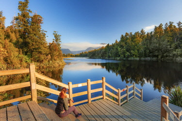NZ9890AW A woman sitting on the jetty enjoying the view of the peaceful Lake Matheson with the Fox glacier and the Southern Alps reflecting in the water at sunset