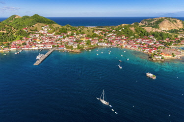 Guadeloupe, Les Saintes, Terre de Haut, the bay of the town of Terre de Haut, listed by UNESCO among the 10 most beautiful bays in the world, Basse Terre background (aerial view)