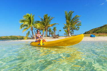 Woman sea kayaking, Waya island, Yasawa island group, Fiji (MR)