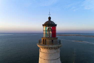HMS3568485 France, Gironde, Verdon-sur-Mer, rocky plateau of Cordouan, lighthouse of Cordouan, classified Historical Monuments, lighthouse keeper at the lantern at sunset (aerial view)
