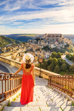 CLKGA115396 Young woman admiring the enchanting hilltop city of Ragusa Ibla from the stairs of Santa maria delle Scale church, Ragusa, Sicily, Italy  (MR)
