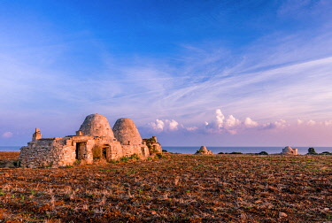 CLKGF114839 Trulli during the sunrise in a dry field with the sea on the background, Polignano a Mare, Apulia, Italy