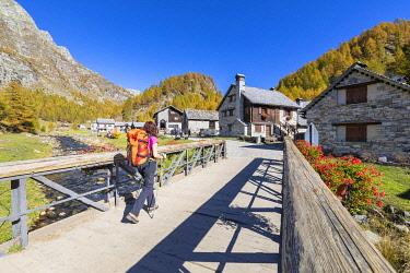 CLKGP119909 A girl is walking at Alp Crampiolo in autumn season, Alpe Veglia and Alpe Devero Natural Park (Alpe Devero, Baceno, Antigorio Valley, Verbano Cusio Ossola province, Piedmont, Italy, Europe) (MR)