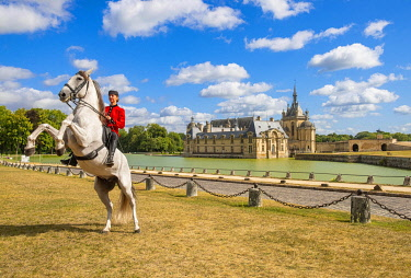 HMS3583261 France, Oise, Chantilly, the castle of Chantilly, the Grandes Ecuries, Estelle, rider of the Grandes Ecuries, makes up her horse in front of the castle