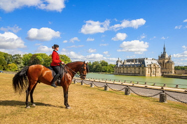 HMS3589693 France, Oise, Chantilly, Chateau de Chantilly, the Grandes Ecuries (Great Stables), Clara rider of the Grandes Ecuries, runs his horse at the Spanish pace in front of the castle