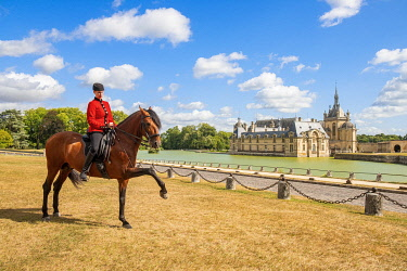 HMS3589696 France, Oise, Chantilly, Chateau de Chantilly, the Grandes Ecuries (Great Stables), Clara rider of the Grandes Ecuries, runs his horse at the Spanish pace in front of the castle