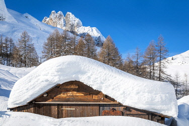 CLKMG121167 landscape of snow-covered mountain huts in the locality Ciamp de Lobia, Fedaia pass, Rocca Pietore, Marmolada, Dolomites, Belluno, Veneto, Italy
