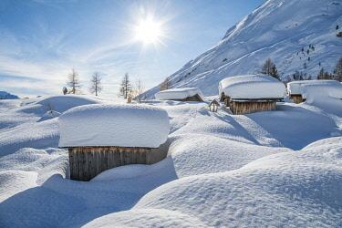 CLKMG121169 landscape of snow-covered mountain huts in the locality Ciamp de Lobia, Fedaia pass, Rocca Pietore, Marmolada, Dolomites, Belluno, Veneto, Italy