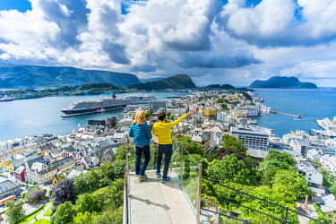 CLKRM116721 Man and woman admiring Alesund from platform at Byrampen viewpoint, Aksla, More og Romsdal county, Norway