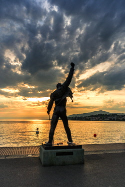CLKRM118455 Dramatic sky at sunset over the Freddie Mercury statue on shores of Lake Geneva, Montreux, Canton� �of Vaud, Switzerland