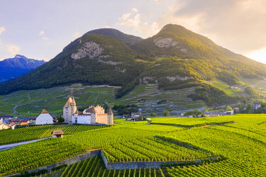 CLKRM118531 Sun rays over Aigle Castle in between green hills and mountains, aerial view, canton of Vaud, Switzerland