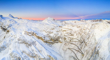 CLKRM120328 Aerial panoramic of Stelvio Pass and winding road covered with snow at dawn, Bormio, Sondrio province, Valtellina, Lombardy, Italy