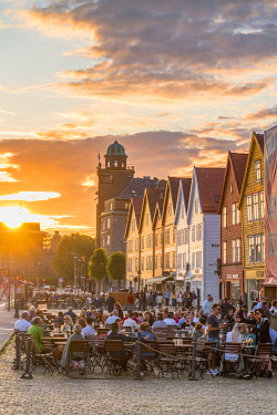 CLKRM120769 People dining and having a drink in the outdoor restaurants of Bryggen at sunset, Bergen, Hordaland County, Norway
