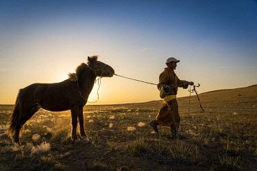 CLKSL120263 Mongolian shepherd wearing traditional dress in steppe of Gobi desert with his hourse, Mongolia