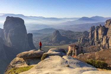 GRE1802AW A man looks at the view above Rousanou Monastery, Meteora, Thessaly, Greece