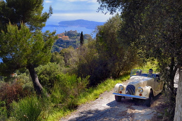 HMS3525556 France, Alpes Maritimes, discovering the coast in a Morgan Roadster 4/4 vintage car, here on a road overlooking the hilltop village of Eze, Saint Jean Cap Ferrat in the background