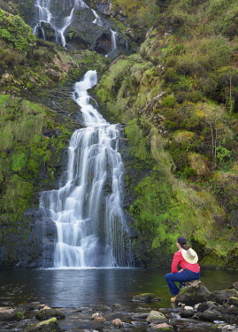 IRL1073AW Ireland, Co.Donegal, Ardara, assaranca waterfall, woman sitting on rock. (MR)
