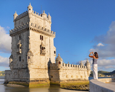Portugal, Lisbon, Belem, Belem Tower, Woman photographing tower (MR)