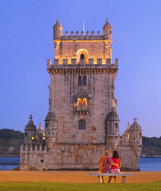 Portugal, Lisbon, Belem, Belem Tower , Man and woman Sitting on bench at dusk (MR)