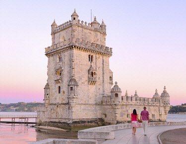 Portugal, Lisbon, Belem, Belem Tower , Man and woman walking by tower (MR)