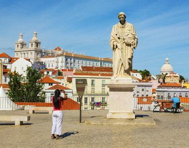 POR10790AW Portugal, Lisbon, The Alfama, the church of Sao Vicente de Fora and the dome of Santa Engracia, Woman photographing statue (MR)