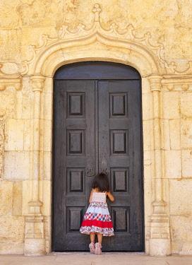 POR10795AW Portugal, Lisbon Jeronimos Monastery, UNESCO World Heritage Site, Girl looking through keyhole (MR)