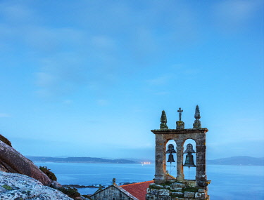 SPA9652 Spain. Galicia. Muxia. Church bells and tower of the Igrexia de Santa Maria overlooking the Ocean in the town of Muxia which is seen by pilgrims on the Camino walking towards Muxia and Finisterre afte...