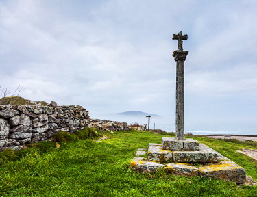 SPA9653 Spain. Galicia. Muxia. An old stone cross overlooking the ocean at Muxia, one of the symbols seen by pilgrims on the Camino towards Muxia and Finisterre.