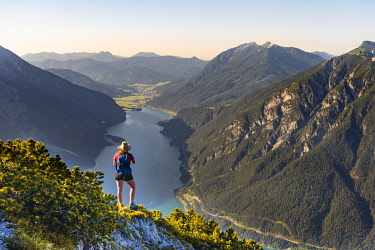 IBXMMW05086810 Young hiker, woman looking into the distance, view from B'renkopf mountain to Lake Achen, left Seebergspitze and Seekarspitze, right Rofan Mountains, Tyrol, Austria, Europe